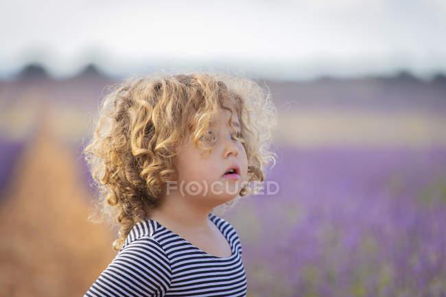 Чарівної маленької дівчинкою фотографіях хтось дивитися вбік у фіолетовий lavender сфера — стокове фото