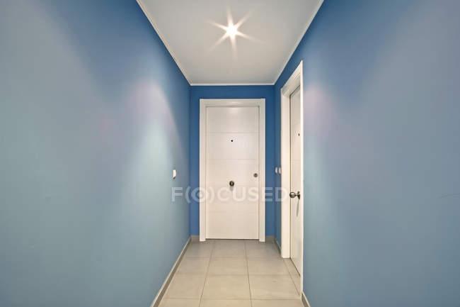 Interior of modern blue corridor with white doors — Stock Photo
