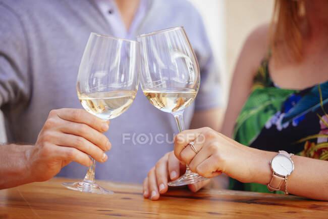 Tiro sem rosto de homem e mulher sentado à mesa e clinking com vinhedos tendo data — Fotografia de Stock