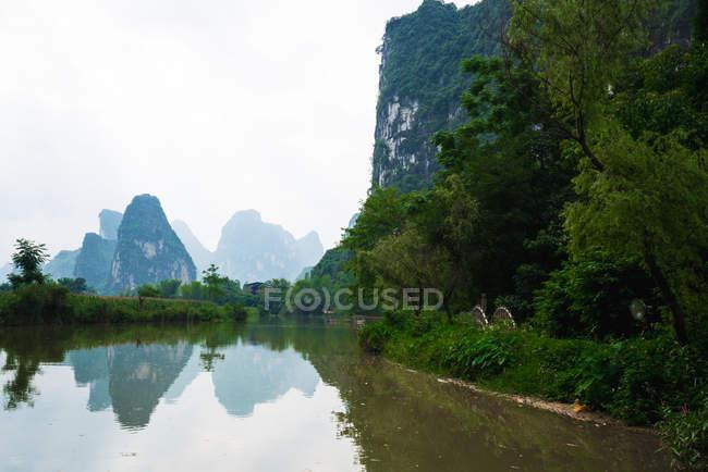 Tranquille rivière Quy Son et silhouette de montagnes sur fond, Guangxi, Chine — Photo de stock
