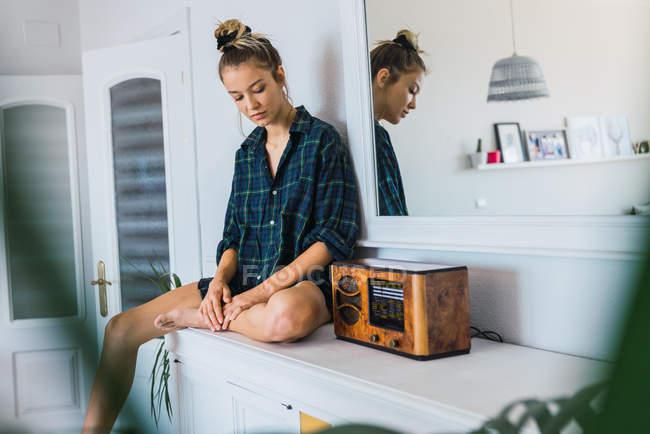 Junge Frau in Übergröße kariertes Hemd sitzt an der Theke in der Nähe von Retro-Funk-Empfänger — Stockfoto