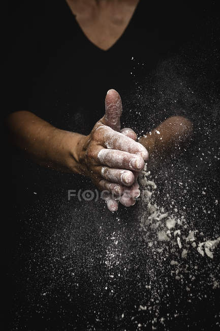 Human hands shaking off flour and pieces of dough on black background — Stock Photo