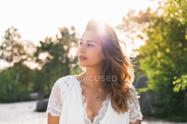 Charming brunette wearing elegant bridal dress with necklace and looking at camera outdoors — Stock Photo
