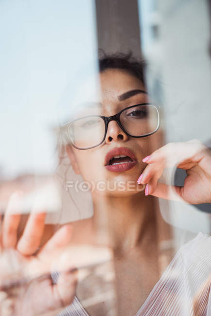 Alluring woman with eyeglasses looking at camera behind window — Stock Photo
