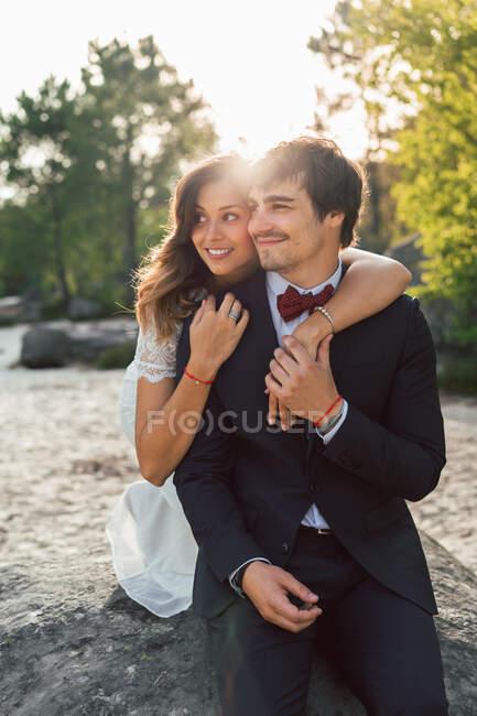 Feliz elegante hombre y mujer en trajes de novia abrazándose en la roca de la playa y mirando sonriente lejos a la luz del sol - foto de stock