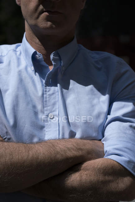 Close-up of man standing with arms crossed — Stock Photo