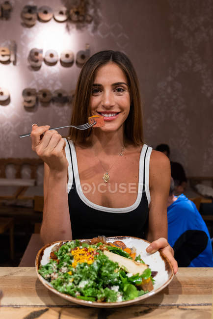 Smiling woman sitting in cafe with bowl of food and looking at camera — Stock Photo