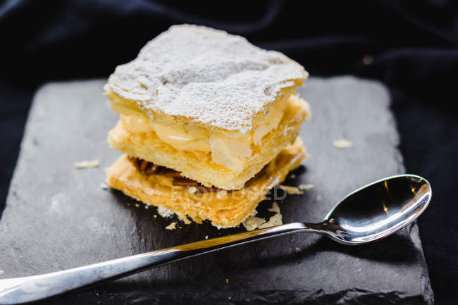Puff pastry dessert with cream on slate on black fabric — Stock Photo