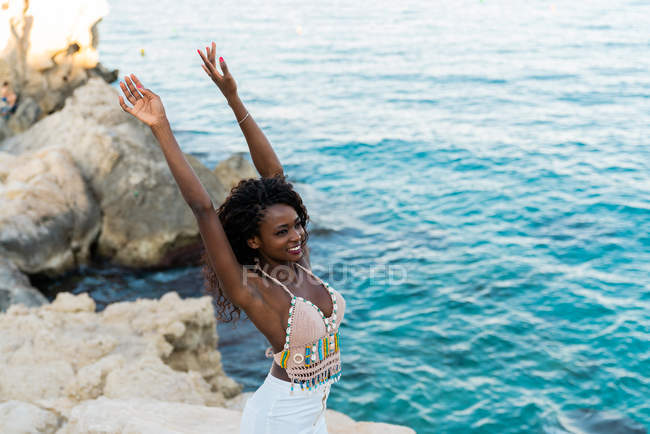 Элегантный черный женщина, стоя на скале с руками над водой — стоковое фото