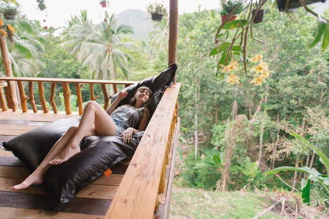 Jovem deitada no terraço na floresta tropical — Fotografia de Stock