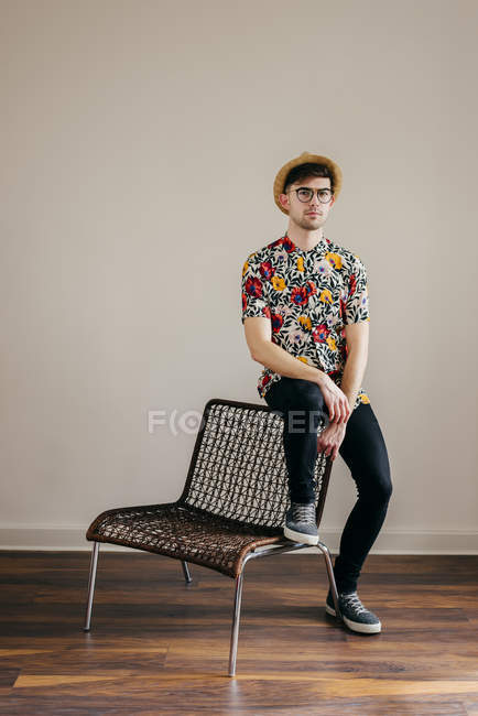 Young stylish man in straw hat and patterned shirt sitting on chair against grey wall — Stock Photo