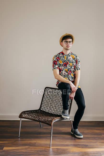 Giovane uomo elegante in cappello di paglia e camicia fantasia seduta sulla sedia contro parete grigia — Foto stock