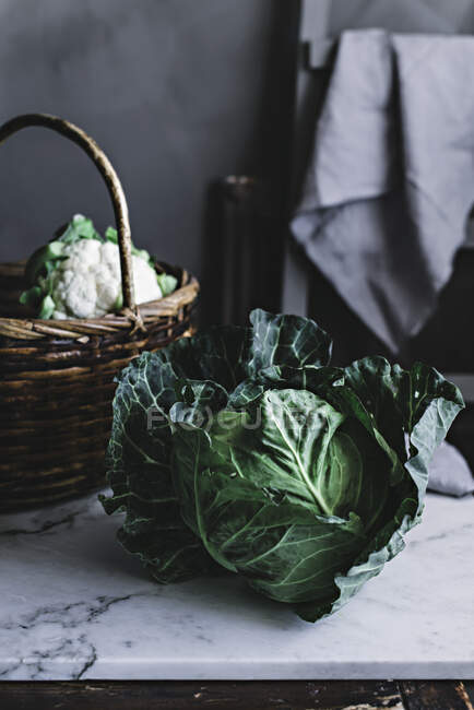 Cabbage lying near basket — Stock Photo