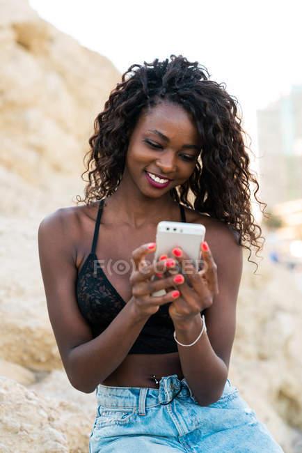 Очаровательная молодая кудрявая женщина с помощью смартфона, сидя на скале — стоковое фото