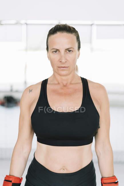Впевнена в собі жінка в боксерські рукавички, стоячи в тренажерний зал — стокове фото