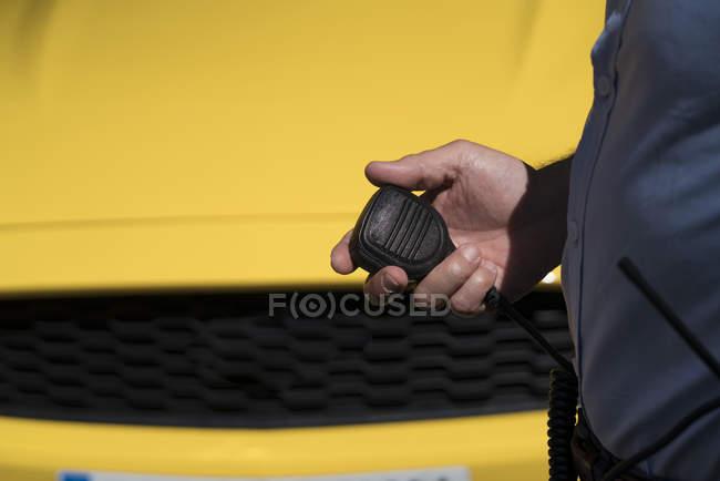 Main du policier tenant le poste de radio portatif à l'extérieur — Photo de stock
