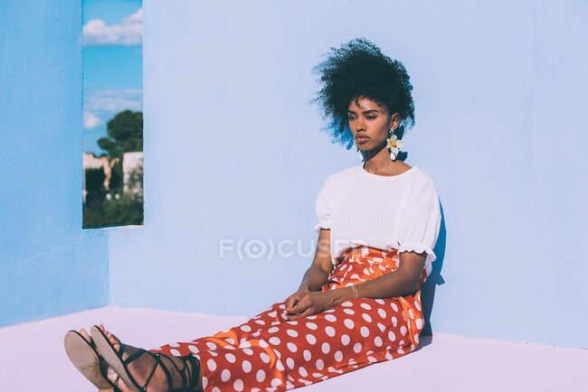 Mujer negra sentada en una colorida terraza geométrica en la azotea - foto de stock