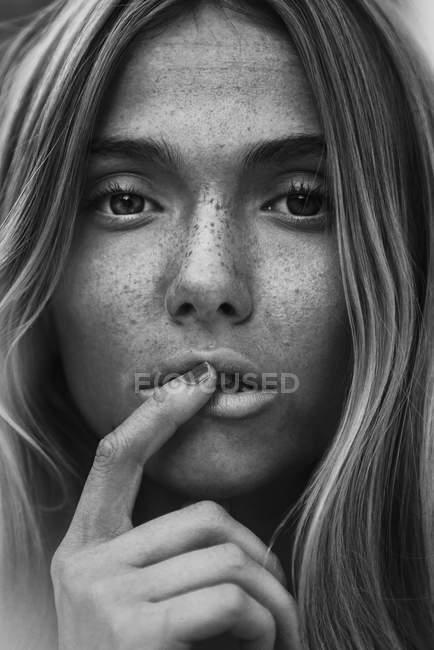 Primo piano di bella bionda giovane donna con lentiggini guardando la fotocamera e toccando le labbra — Foto stock