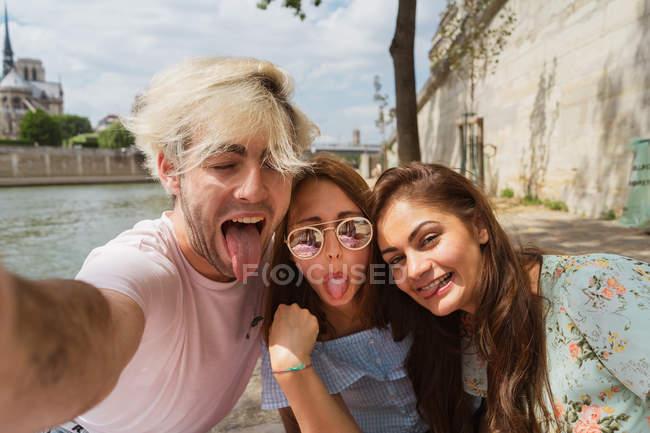 Sorridente giovane donna e uomo in abiti casual prendendo selfie all'aperto — Foto stock