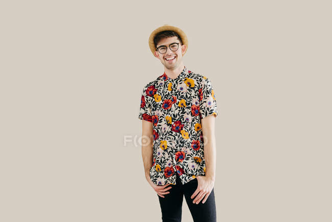 Young stylish man in straw hat and patterned shirt posing against grey wall — Stock Photo