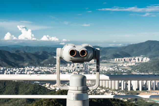 White construction of coin binocular viewer on terrace against cityscape in tropical mountains, Phoenix Park, China — Stock Photo