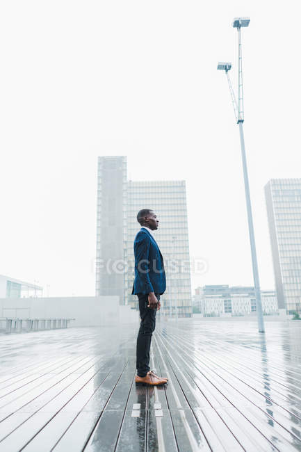 Elegant businessman standing on pavement in rain against modern city buildings — Stock Photo