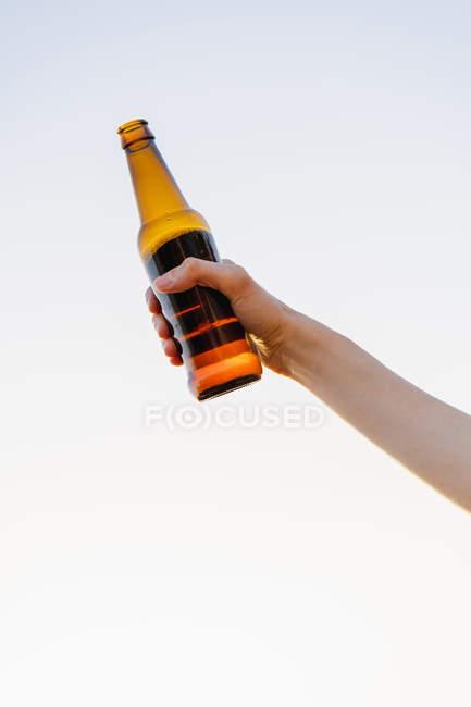 Жіночий руки, що тримає пляшку пива проти неба — стокове фото