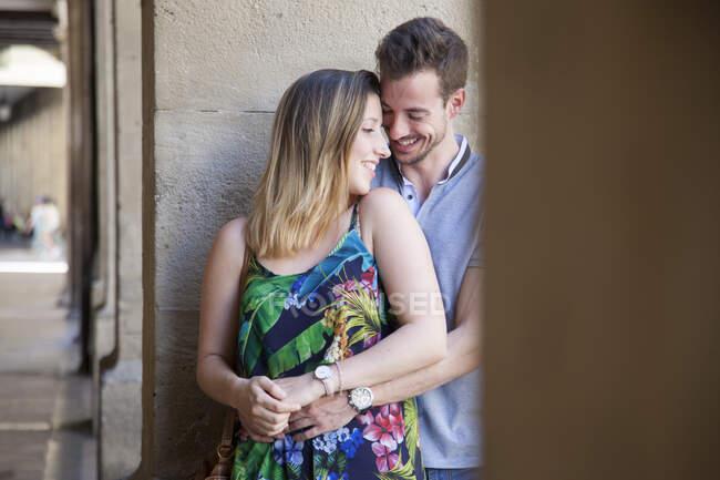 Hermoso joven hombre y mujer abrazándose tiernamente mientras se apoya en la pared afuera mirándose el uno al otro - foto de stock
