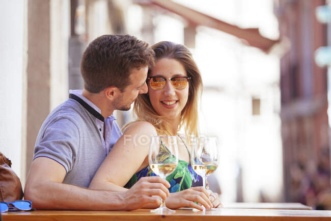 Couple talking with wineglasses at terrace — Stock Photo