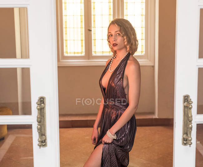 Elegant blonde woman in evening dress standing in doorway of luxury house and looking at camera — Stock Photo