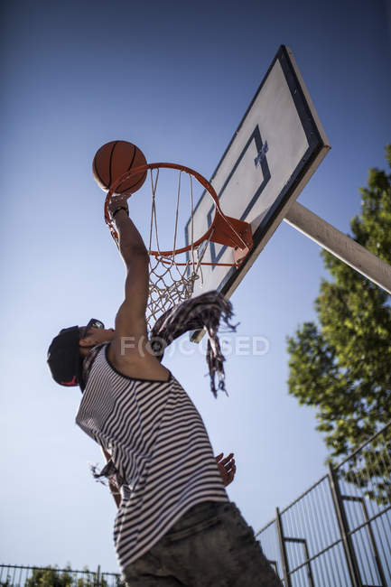 Afro young boy aiming basketball in basket on court outdoors — Stock Photo