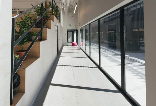 Перспективный вид коридора со стеклянными окнами и дверным проемом в конце в офисном интерьере — стоковое фото
