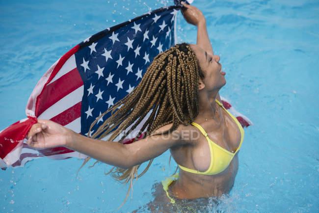 Счастливая женщина, стоящая в бассейне, наслаждаясь американским флагом — стоковое фото
