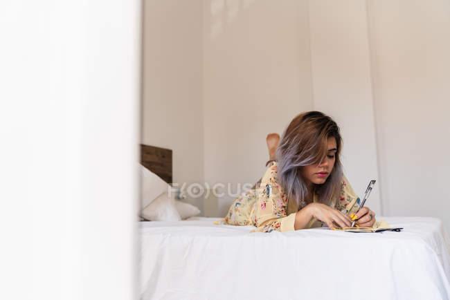 Молодая женщина в шелковом халате лежит на кровати и делает наброски в блокноте в стильной спальне — стоковое фото