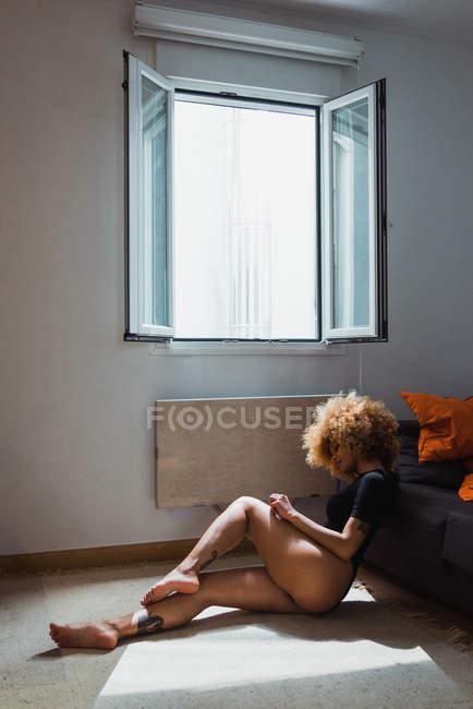 Чуттєва жінка етнічних в боді, сидячи на підлозі будинку — стокове фото