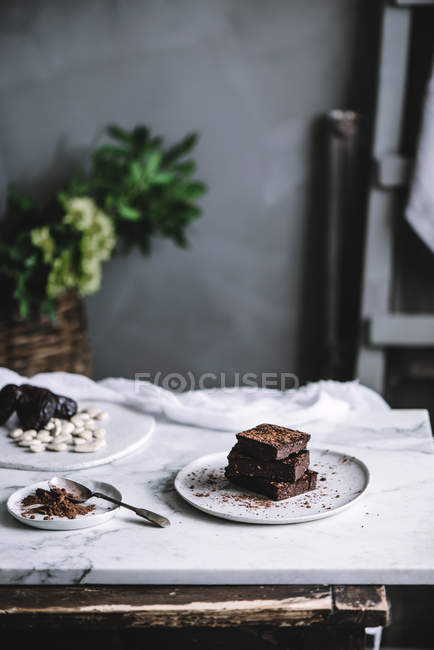 Tasty sweet vegan brownie dessert and cocoa powder on plates on table — Stock Photo