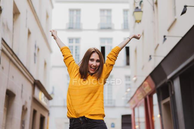 Mulher sorridente em cardigan amarelo em pé na rua com as mãos para cima — Fotografia de Stock