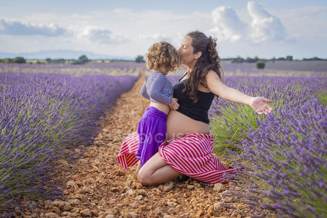 Happy pregnant woman kissing little daughter while sitting on pathway in blooming lavender field — Stock Photo