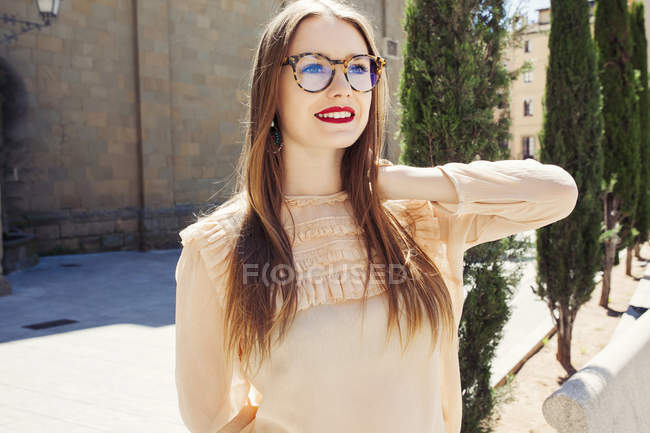 Улыбающаяся стильная женщина в очках, стоящая снаружи — стоковое фото