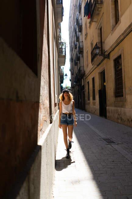 Affascinante donna riccia in pantaloncini e stivali brutali in piedi giocosamente sulla strada asfaltata divertirsi — Foto stock
