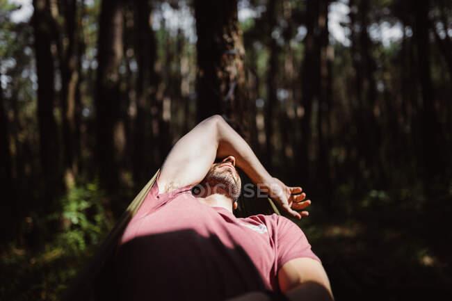 Persona acostada en hamaca verde entre árboles en bosque en Cantabria, España - foto de stock
