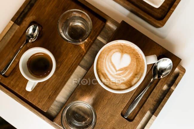 Верхній вигляд чашки лате з маленьким серцем на дерев'яній дошці.. — стокове фото