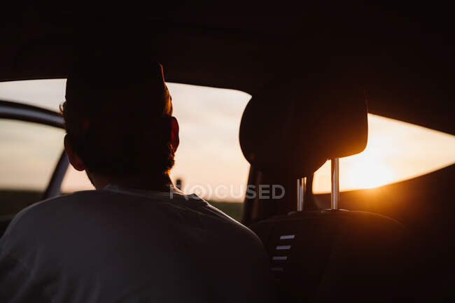 Back view of guy sitting in coupe car and watching picturesque sundown in Cantabria, Spain — Stock Photo