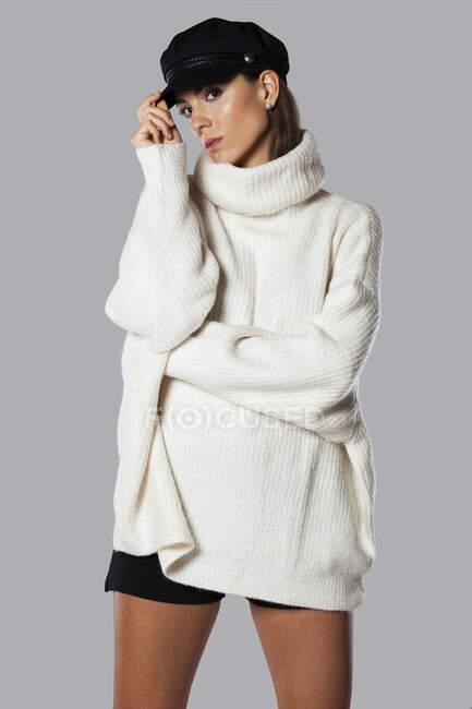 Bella giovane bruna in pigiama con pantaloncini e calze sportive al ginocchio seduta su sfondo bianco. — Foto stock