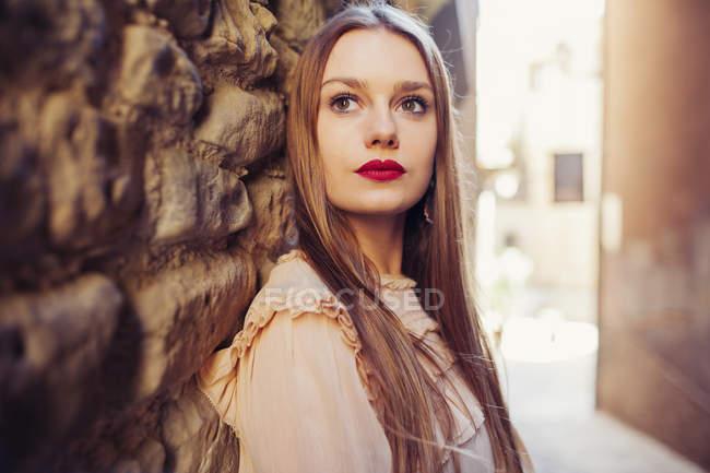 Молода жінка вдумливі, спираючись на кам'яну стіну на відкритому повітрі — стокове фото