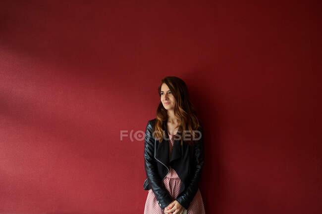 Giovane donna in giacca in piedi vicino al muro rosso — Foto stock