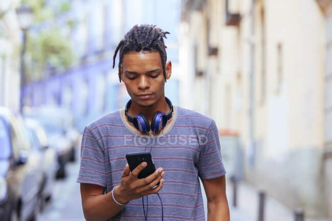 African American guy in headphones on street — Stock Photo