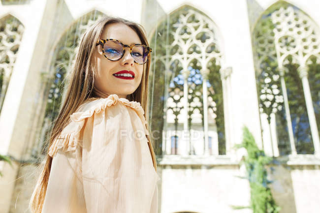 Young woman with red lips wearing trendy glasses and looking flirty at camera against urban architecture — Stock Photo