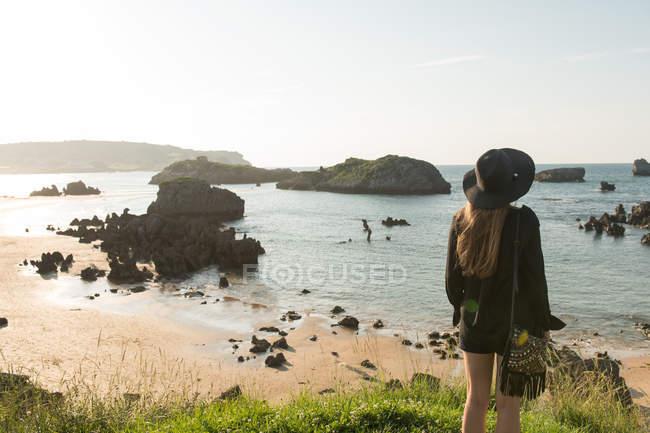 Frau mit Hut stehen auf dem Rasen an Küste und genießen Blick auf Meer an sonnigen Tag — Stockfoto
