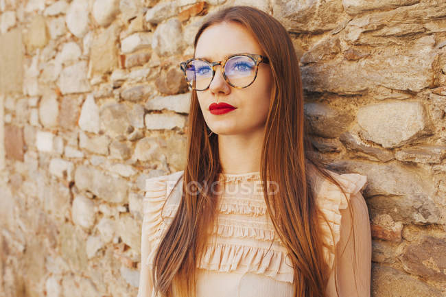 Stylish thoughtful woman in glasses leaning on stone wall outdoors — Stock Photo